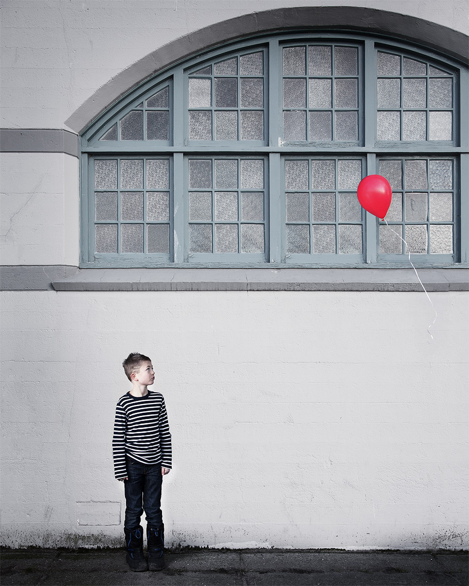 Boy looking at his red balloon flying away.