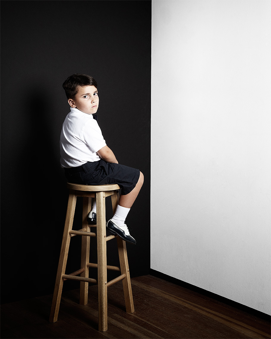 Portrait of an unhappy  kid sitting in a corner corner